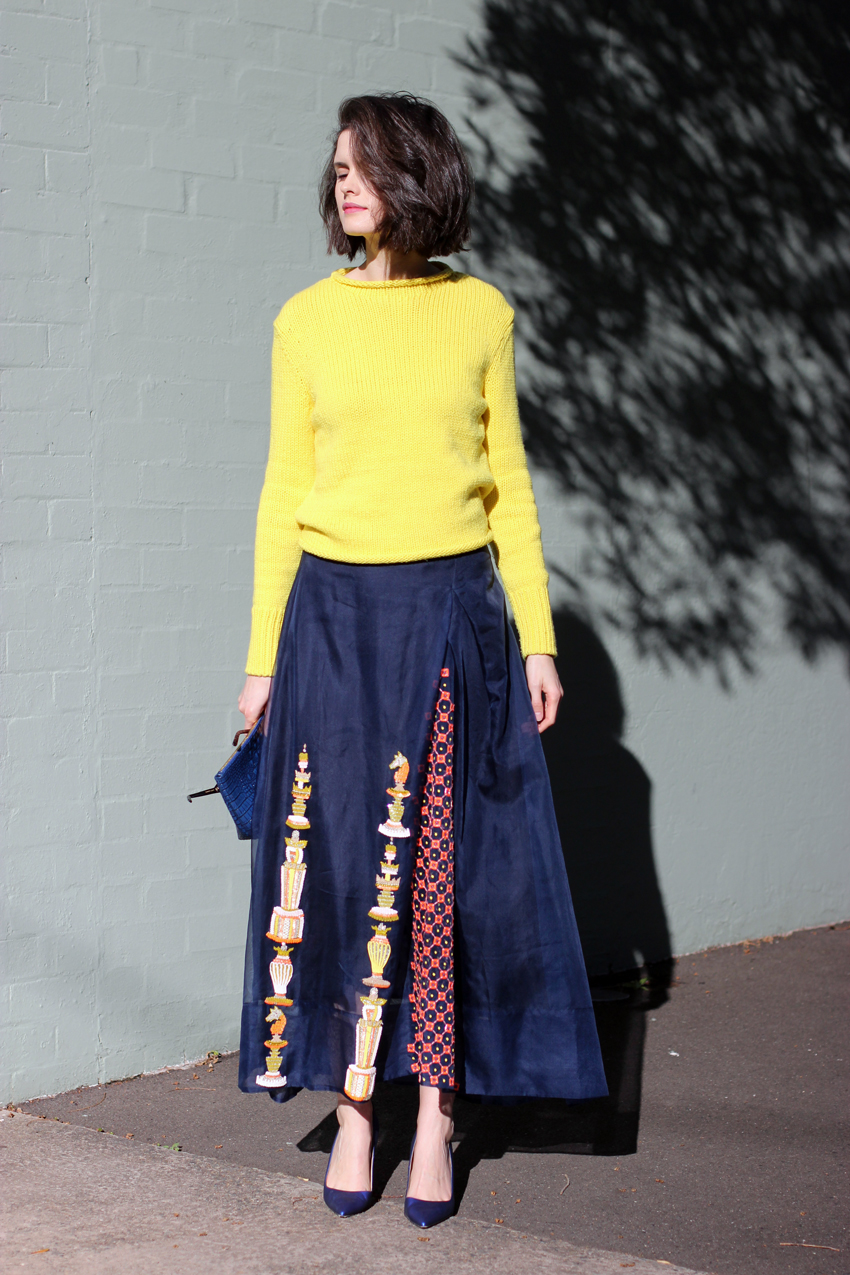 Chloe-Hill-in-Cos-yellow-jumper,-after-the-apple-clutch,-Easton-Pearson-beaded-full-legnth-skirt-and-manolo-Blahnik-blue-heels