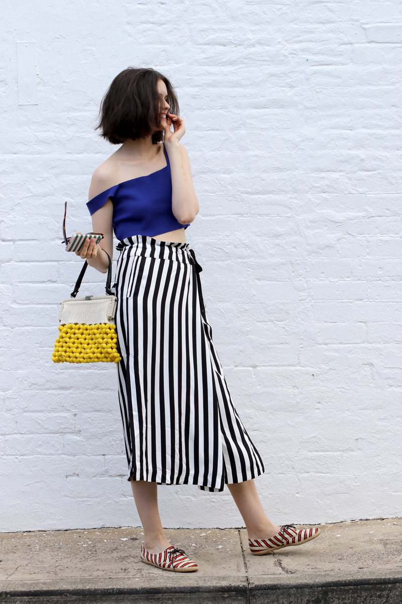 Chloe Hill Wearing Marni blue crop top and beaded bag, Lee Mathews stripe wrap skirt and Tabitha Simmons striped shoes in Sydney